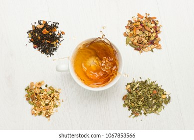 cup with splashing tea on white table with variety of herbal tea
