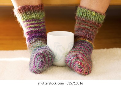 cup standing between two feet wearing knitted socks