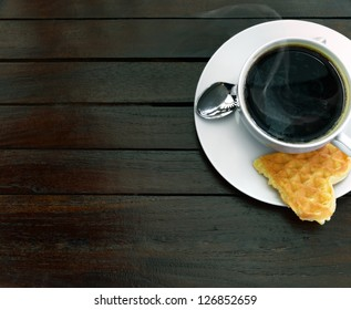 Cup of steaming coffee and a fresh waffle