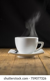 Cup of steaming hot coffee on old wooden table