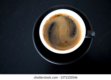 Cup of strong black coffe on wooden table