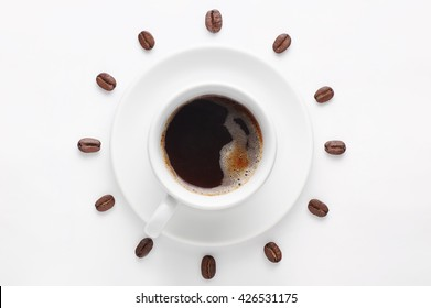 Cup of strong coffee with foam on saucer and coffee beans against white background forming clock dial viewed from above. Coffee as symbol of morning energy and cheerfulness or evening refreshment.
