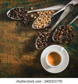 Cup of strong espresso coffee with assorted roasted and raw beans spilling over from four vintage silver spoons on a rustic wood background with copy space