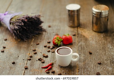 A cup of strong spicy hot coffee witn chile pepper, strawberry, coffee beans and lavender on wooden background