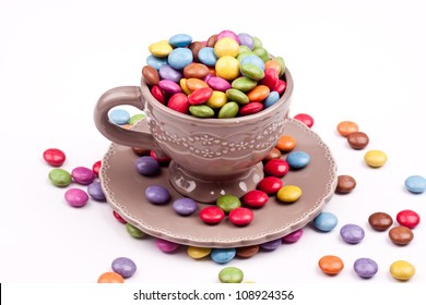 a cup of sugar coated chocolate pills