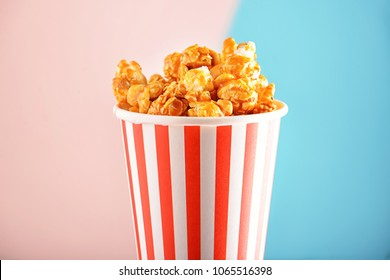 Cup with tasty caramel popcorn on color background