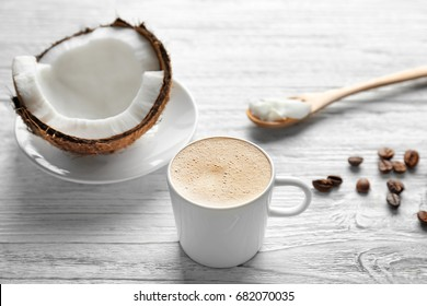 Cup of tasty coconut coffee and nut on wooden table