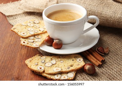 Cup of tasty coffee with Italian biscuit, on wooden background