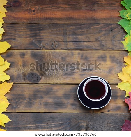 5eb94b811b4 A cup of tea among a set of yellowing fallen autumn leaves on a background  surface