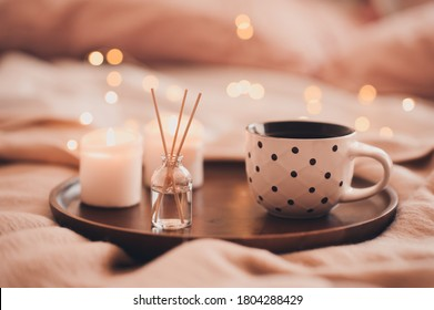 Cup of tea with aroma sticks and burning candles in bed staying on wooden tray closeup. Good morning. Winter holiday season. Cozy atmosphere.  - Shutterstock ID 1804288429
