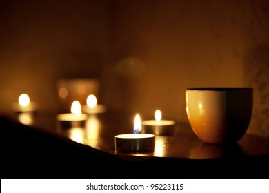 Cup of tea and aromatic candles in the dark