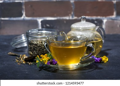 cup of tea with aromatic herbs on a dark background, horizontal