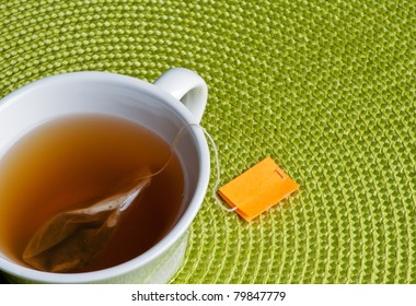 Cup of tea with bag and green place mat.