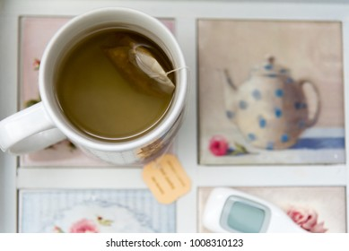 Cup of tea with tea bag on tray with digital thermometer
