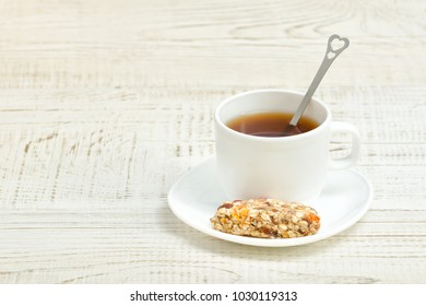 Cup of tea and a bar of muesli. White wooden background