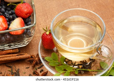 cup of tea and berry dessert on a wooden background