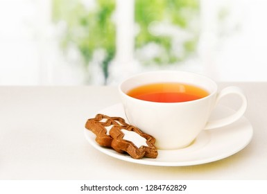Cup with tea and biscuits on a saucer on the table