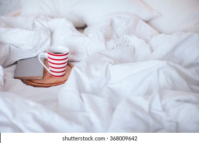 cup of tea and a book lying on a white bed
