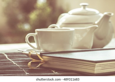 cup of tea and book - a book on the table with a pot of tea and a cup - concept of lazy afternoon teatime, relaxation, quietness and desire for reading - vintage style color fading