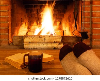 Cup of tea, book, women's feet in warm socks on a wooden table opposite a burning fireplace