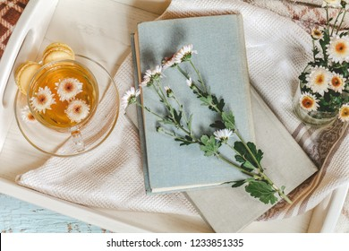 Cup of tea, books, chrysanthemum flowers and macaroons in tray on the table. Cozy home concept. Coloring and processing photo in cinematic style.