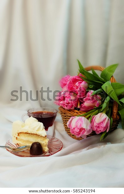 A cup of tea, a bouquet of tulips in a basket a piece of cake and candy.
