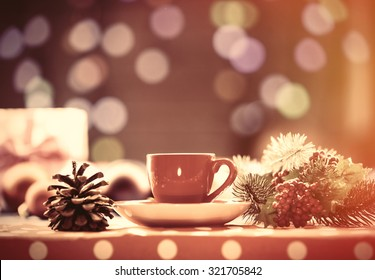 Cup of tea and branch with Christmas lights on background.