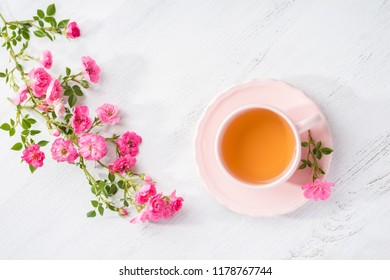 Cup of tea and branch of small pink  roses on rustic table. Flat lay