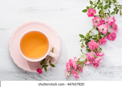 Cup of tea and branch of small pink  roses on rustic table