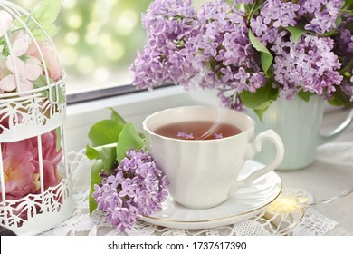 cup of tea and bunch of purple lilac blossoms on window sill in romantic mood