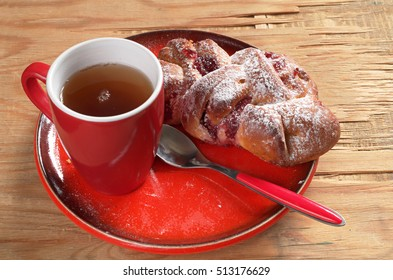 Cup of tea and buns with jam in red plate on old wooden table