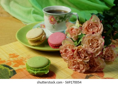 A cup of tea, cake macaroon, pink roses on a background of green fabric.