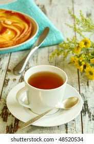 cup of tea, cake and yellow flowers on old wooden