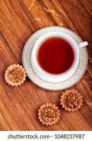 Cup of tea with cakes on a wooden background, top view