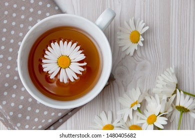 cup of tea camomile in it on a brown polka dot fabric on a white background  top view copy space