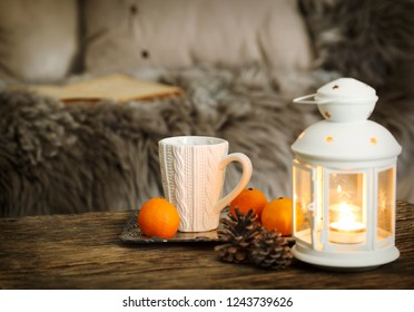 Cup of tea and candles on wooden table near the sofa with pillows
