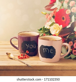 Cup of tea with chalkboard stickers and flowers on wooden table