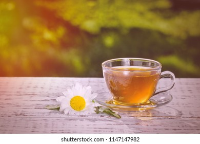 A cup of tea with chamomile, close-up, lit by sunlight, on a white wooden table.