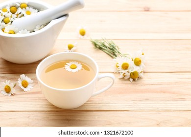 Cup of tea with chamomile flowers on brown wooden table
