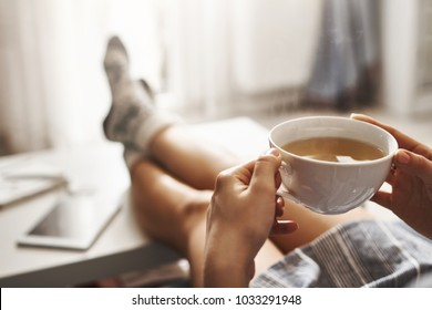 Cup of tea and chill. Woman lying on couch, holding legs on coffee table, drinking hot coffee and enjoying morning, being in dreamy and relaxed mood. Girl in oversized shirt takes break at home - Shutterstock ID 1033291948
