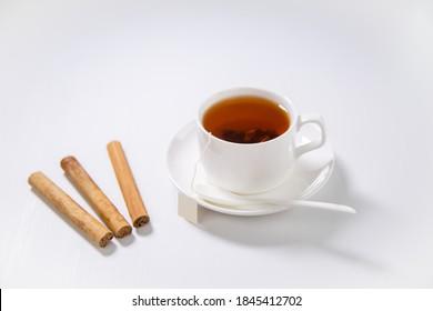 A cup of tea, Cinnamon tea, Cinnamon drink with cinnamon stick on a Tea Bag on a white background, Spoon, Ceylon Tea, Sri lanka, Ceylon Cinnamon