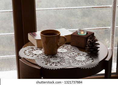 The cup of tea or coffee with a book and candle on the wooden table near the window on the rainy weather.