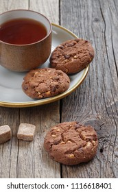 Cup of tea and cookies with chocolate and nuts in plate on the old wooden table