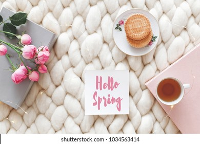 Cup of tea, cookies, pink rose flowers, book and card with text Hello Spring on white knitted woolen merino chunky blanket. Breakfast in bed. Cozy spring homely scene. Flat lay, top view. Home decor.