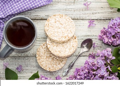 Cup of tea with crispbreads decorated spring lilac flowers on white wooden background. Top view