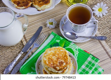 cup with tea, curd pancakes on a dish and milk