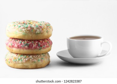 A cup of tea and doughnuts on white background