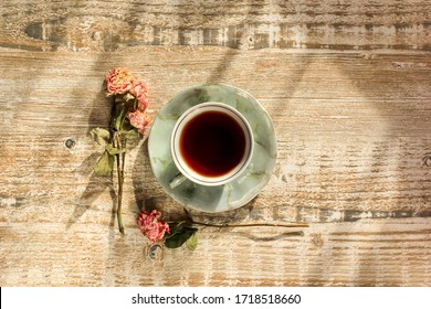 Cup of tea and dry rose flowers on light textured wooden table with sunlight and shadows. Concept of relax, holidays, weekends.
