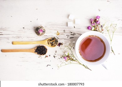 A cup of tea with flowers and tea around it
