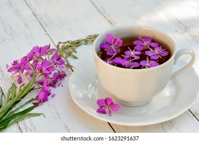 Cup of tea with flowers of fireweed on white wooden background  closeup